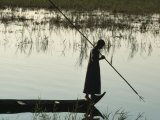 Woman Stands at the End of a Rowboat with a Fishing Spear