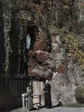 Two People Stand in Front of a Replica of the Grotto of Lourdes