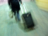 Unrecognizable Person Dragging Luggage Through San Francisco Airport