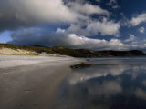 Sunlight Pierces Storm Clouds Illuminating an Empty and Remote Beach