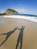 Shadow of a Couple Holding Hands on a Beach as Gentle Surf Rolls In