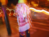 Young Person in Colorful Garb Walking a San Francisco Street at Night