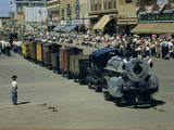People Watch a Miniature Train Parade on Main Street