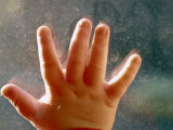 Close View of a Small Child&#39;s Hand on Dirty Glass