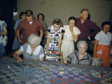 Women Demonstrate How to Make a Patchwork Quilt at a Festival