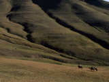 Three People on Horseback in a Landscape of Folding Hills