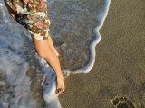 Frothy Waves Lap Up Against a Woman&#39;s Bare Feet