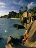 Woman Sits on a Rock on La Digue Island in the Seychelles