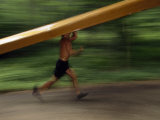 Man Carrying a Rowing Scull While Running