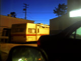 Trailer and Cars Parked Behind a Gas Station at Twilight