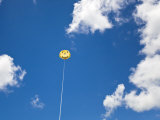 Yellow Smiley Face Parasail in Blue Skies with Nice Puffy Clouds