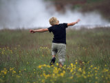 Boy Runs Through a Field of Grass and Yellow Flowers