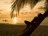 Woman Resting on a Palm Tree at Sunset  Sunset over the Caribbean Sea