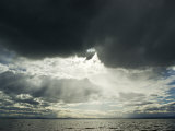 Sunrays Pierce an Ominous Black Storm Cloud on a Vast Freshwater Lake