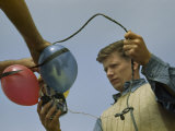 Man Holds Electrical Leads to Equipment Tied to Flotation Balloons