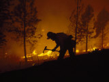 Firefighter Silhouetted on Hill Battling a Forest Fire at Night