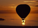Riding in a Hot Air Balloon over Water at Sunset