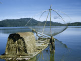 Fisherman Stands in Canoe Beside Raft with Hut and Fishing Net