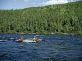 Men Paddle a Canoe Through River Rapids