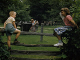 Girl and Boy Climb a Split Rail Fence in a State Park