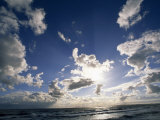 Beach with Gentle Surf under a Sky Filled with Puffy Clouds