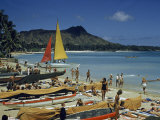 People Sunbathe and Walk on Sand Past Beached Outrigger Canoes