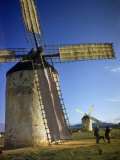 People with a Dog Stand Beside a Giant Windmill