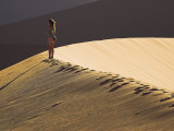 Young Woman Walks across the Dunes at Sunset at Sossusvlei  Namibia