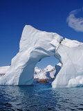 Grandidier Channel  Tourists Zodiac Cruising by Arched Iceberg Near Booth Island  Antarctica