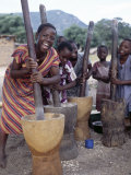Cheerful Young Girls Pound Corn Outside Families' Homes Near Monkey Bay  South End of Lake Malawi