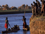 Dassanech Tribesmen and Women Load into a Dugout Canoe Ready to Pole across the Omo River  Ethiopia