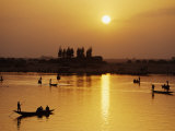 Boats Plying the River with the Sun Sinking Behind Them and the Far Bank of the River Niger
