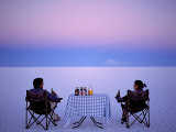 Tourists Enjoy Sundowners While Looking Out across the Endless Salt Crust of Salar De Uyuni