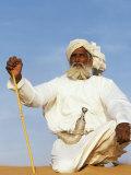 Bedouin Man Kneels on Top of a Sand Dune in the Desert