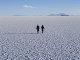 Two Tourists Walk across the Endless Salt Crust of Salar De Uyuni  the Largest Salt Flat in World