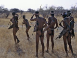 Bushmen or San Hunter-Gatherers Pause to Check a Distant Wild Animal in the Early Morning  Namibia