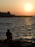 Fisherman Watches as the Sun Goes Down on the Waterfront of Alexandria  Egypt