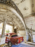 Classic Red American Car Parked Beneath Ornate Marble Staircase Inside Apartment Building