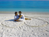 Young Couple on Beach Sitting in a Heart Shaped Imprint on the Sand  Maldives  Indian Ocean  Asia