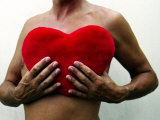 Man Holding Red Heart-Shaped Cushion in Front of His Naked Chest