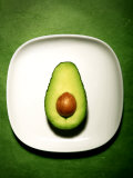 Half an Avocado on a White Plate