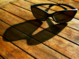 Sunglasses and their Shadow on a Wooden Table