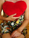 Lady Sitting with Red Cushion Heart Against Her Chest