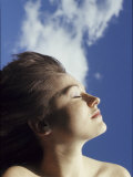 Young Woman Profiled Against a Cloud Filled Sky on a Sunny Day