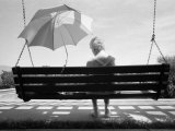 Woman with Alzheimer's Sits on a Swing Shaded by an Umbrella