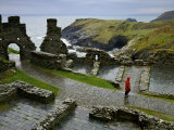 Tourist Walks the Paths of Tintagel Castle Overlooking the Coast