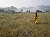 Female Shaman Walks across Grass in a Bright Yellow Silk Robe
