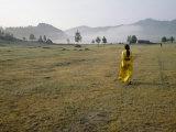 Female Shaman Walks across Grass in a Bright Yellow Silk Robe