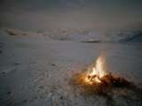 Campfire Burns in a Snow Covered High Altitude Landscape