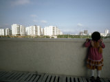 Little Girl Looks over a Wall Toward High Rises Near Hong Kong